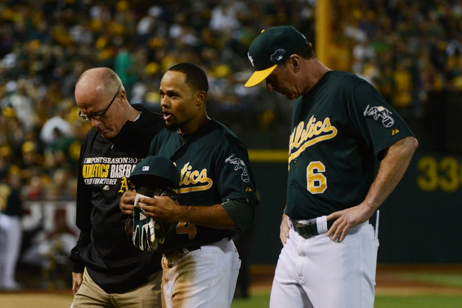 October 4, 2013; Oakland, CA, USA; Oakland Athletics center fielder Coco Crisp (4, center) talks to manager Bob Melvin (6) and assistant trainer Walt Horn (left) after the eighth inning in game one of the American League divisional series playoff baseball game against the Detroit Tigers at O.co Coliseum. The Tigers defeated Athletics 3-2. Mandatory Credit: Kyle Terada-USA TODAY Sports