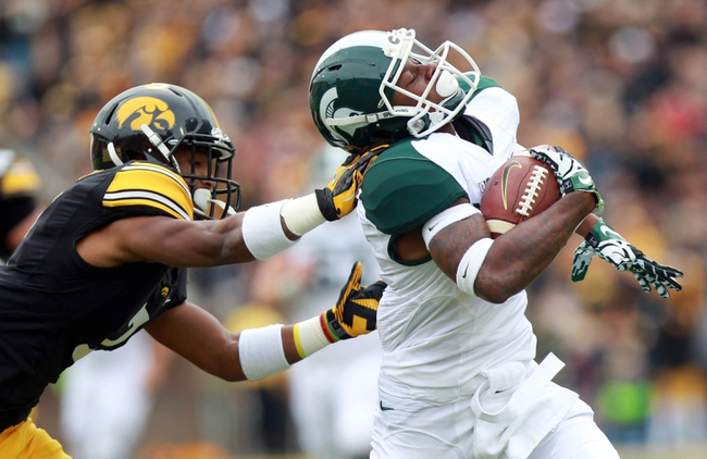 Oct 5, 2013; Iowa City, IA, USA;  Michigan State Spartans receiver Macgarrett Kings Jr. avoids the tackle by Iowa Hawkeyes cornerback Sean Draper (7) at Kinnick Stadium. Mandatory Credit: Reese Strickland-USA TODAY Sports