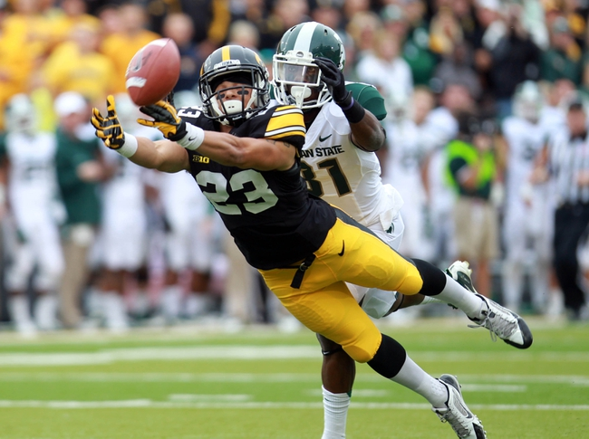 Oct 5, 2013; Iowa City, IA, USA;  Iowa Hawkeyes receiver Jordan Cotton (23) dives for a pass while defended by Michigan State Spartans player Darqueze Dennard (31) at Kinnick Stadium. Mandatory Credit: Reese Strickland-USA TODAY Sports
