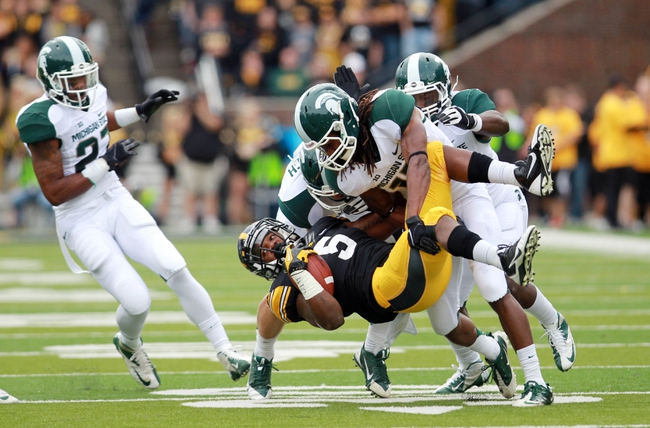Oct 5, 2013; Iowa City, IA, USA;  Michigan State Spartans cornerback Trae Waynes (15) tackles Iowa Hawkeyes receiver Damon Bullock (5) during the game at Kinnick Stadium. Mandatory Credit: Reese Strickland-USA TODAY Sports