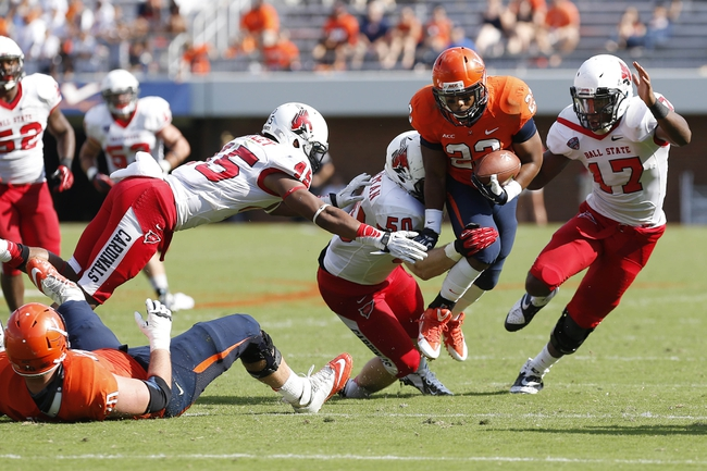 Oct 5, 2013; Charlottesville, VA, USA; Virginia Cavaliers running back Khalek Shepherd (23) carries the ball as Ball State Cardinals linebacker Trent Toothman (50) and Cardinals safety Dae'Shaun Hurley (45) make the tackle in the fourth quarter at Scott Stadium. The Cardinals won 48-27. Mandatory Credit: Geoff Burke-USA TODAY Sports