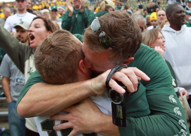 Oct 5, 2013; Iowa City, IA, USA;  Michigan State Spartans quarterback Connor Cook (18) gets a hug from his dad following the teams win against the Iowa Hawkeyes at Kinnick Stadium. Michigan State beat Iowa 26-14.  Mandatory Credit: Reese Strickland-USA TODAY Sports