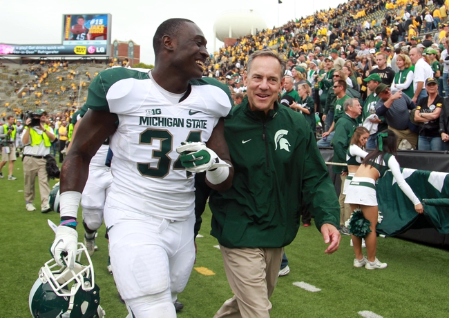 Oct 5, 2013; Iowa City, IA, USA;  Michigan State Spartans coach Mark Dantonio walks of the field with linebacker Taiwan Jones (34) after their game against the Iowa Hawkeyes at Kinnick Stadium. Michigan State beat Iowa 26-14.  Mandatory Credit: Reese Strickland-USA TODAY Sports