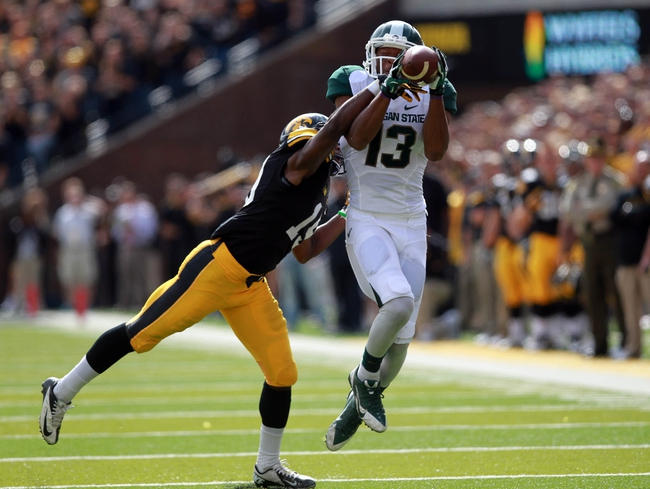 Oct 5, 2013; Iowa City, IA, USA;  Iowa Hawkeyes cornerback B.J. Lowery (19) defends a pass play to Michigan State Spartans receiver Bennie Fowler (13) at Kinnick Stadium. Michigan State beat Iowa 26-14.  Mandatory Credit: Reese Strickland-USA TODAY Sports
