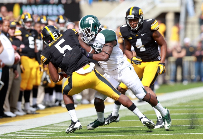 Oct 5, 2013; Iowa City, IA, USA;  Iowa Hawkeyes running back Damon Bullock (5) is tackled by Michigan State Spartans linebacker Anthony Hitchens (31) at Kinnick Stadium. Michigan State beat Iowa 26-14.  Mandatory Credit: Reese Strickland-USA TODAY Sports