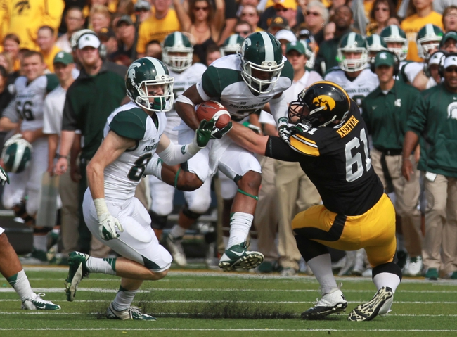 Oct 5, 2013; Iowa City, IA, USA;  Iowa Hawkeyes long snappertackles Michigan State Spartans running back Jeremy Langford (33) at Kinnick Stadium. Michigan State beat Iowa 26-14.  Mandatory Credit: Reese Strickland-USA TODAY Sports