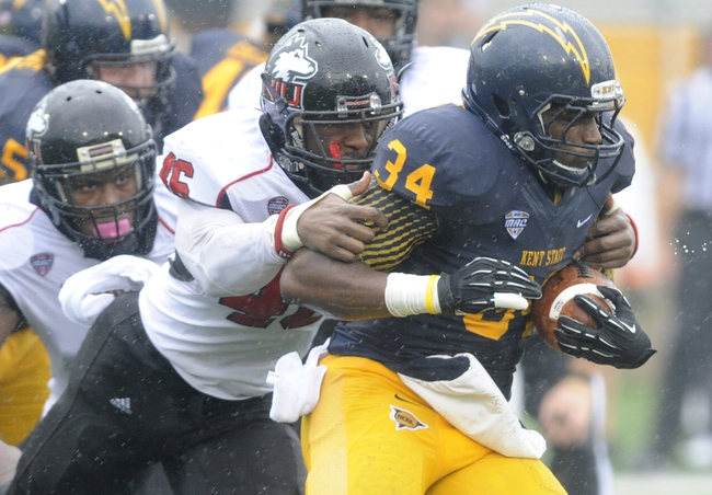 Oct 5, 2013; Kent, OH, USA; Kent State Golden Flashes running back Trayion Durham (34) runs as Northern Illinois Huskies defensive end George Rainey (46) makes the tackle during the first quarter at Dix Stadium. Mandatory Credit: Ken Blaze-USA TODAY Sports