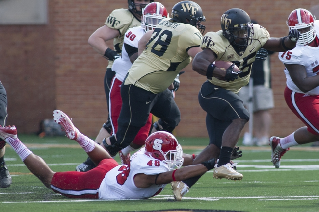 Oct 5, 2013; Winston-Salem, NC, USA; Wake Forest Demon Deacons running back Josh D. Harris (25) runs the ball while North Carolina State Wolfpack linebacker Bryan Smith (48) tries to pull him down from behind during the first quarter at BB&T Field. Mandatory Credit: Jeremy Brevard-USA TODAY Sports