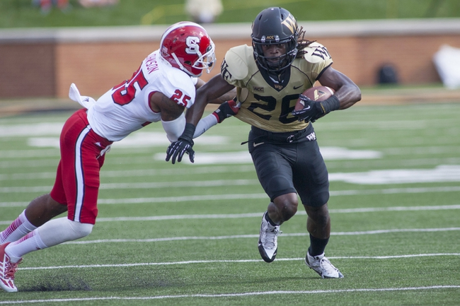 Oct 5, 2013; Winston-Salem, NC, USA; Wake Forest Demon Deacons wide receiver Sherman Ragland III (26) runs after making a catch while being pursued by North Carolina State Wolfpack cornerback Dontae Johnson (25) during the first quarter at BB&T Field. Mandatory Credit: Jeremy Brevard-USA TODAY Sports