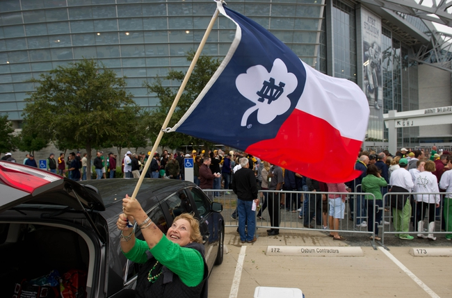 Oct 5, 2013; Arlington, TX, USA; Barbara Burns of San Antonio, Texas, takes down her Notre Dame themed Texas state flag outside AT&T Stadium before the game between the Notre Dame Fighting Irish and the Arizona State Sun Devils. Mandatory Credit: Matt Cashore-USA TODAY Sports