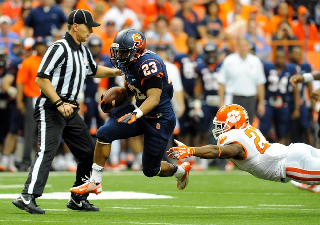 Oct 5, 2013; Syracuse, NY, USA; Syracuse Orange running back Prince-Tyson Gulley (23) runs with the ball in front of the diving tackle attempt of Clemson Tigers safety Robert Smith (27) during the third quarter at the Carrier Dome.  Clemson defeated Syracuse 49-14.  Mandatory Credit: Rich Barnes-USA TODAY Sports