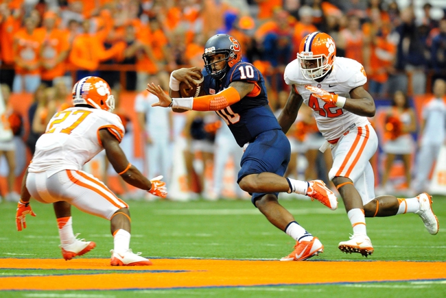Oct 5, 2013; Syracuse, NY, USA; Syracuse Orange quarterback Terrel Hunt (10) runs with the ball splitting the defense of Clemson Tigers safety Robert Smith (27) and linebacker Stephone Anthony (42) during the third quarter at the Carrier Dome.  Clemson defeated Syracuse 49-14.  Mandatory Credit: Rich Barnes-USA TODAY Sports