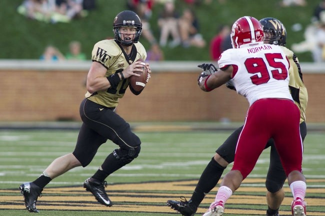 Oct 5, 2013; Winston-Salem, NC, USA; Wake Forest Demon Deacons quarterback Tanner Price (10) rolls outside during the third quarter against the North Carolina State Wolfpack at BB&T Field. Wake defeated North Carolina State 28-13. Mandatory Credit: Jeremy Brevard-USA TODAY Sports