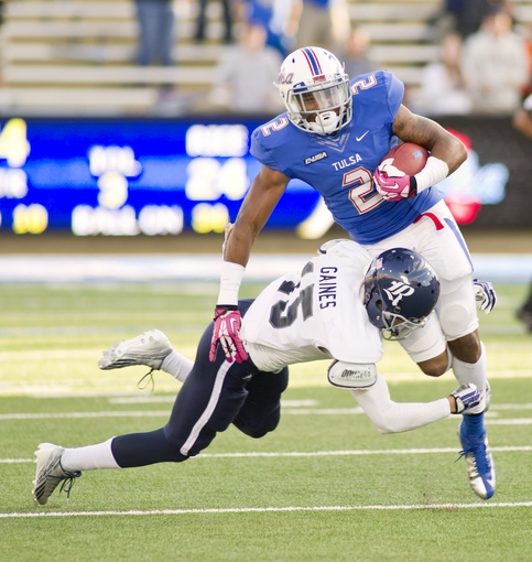 Oct 5, 2013; Tulsa, OK, USA; Rice Owls safety Jaylon Finner (25) tackles Tulsa Hurricanes wide receiver Keevan Lucas (2) during the second half of a game at Skelly Field at H.A. Chapman Stadium. Rice defeated Tulsa 30-27 in an overtime. Mandatory Credit: Beth Hall-USA TODAY Sports