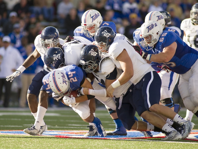 Oct 5, 2013; Tulsa, OK, USA; Tulsa Hurricanes running back Zack Langer (24) is brought down by Rice Owls safety Julius White (7) and linebacker Alex Lyons (41) and safety Paul Porras (24) and defensive back Tanner Leland (13) during the second half of a game at Skelly Field at H.A. Chapman Stadium. Rice defeated Tulsa 30-27 in an overtime. Mandatory Credit: Beth Hall-USA TODAY Sports