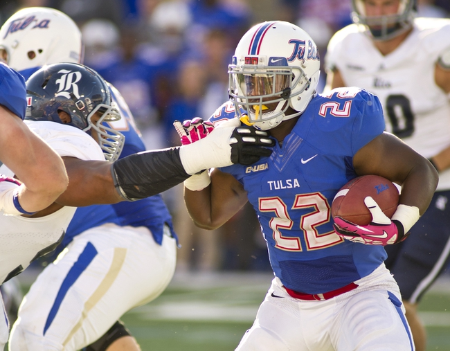 Oct 5, 2013; Tulsa, OK, USA; Tulsa Hurricanes running back Trey Watts (22) carries the ball past a Rice Owls defender during the second half of a game at Skelly Field at H.A. Chapman Stadium. Rice defeated Tulsa 30-27 in an overtime. Mandatory Credit: Beth Hall-USA TODAY Sports