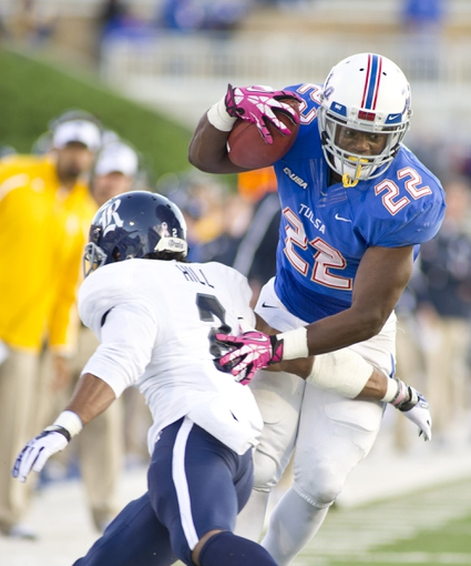 Oct 5, 2013; Tulsa, OK, USA; Tulsa Hurricanes running back Trey Watts (22) gets past Rice Owls safety Malcolm Hill (2) during the second half of a game at Skelly Field at H.A. Chapman Stadium. Rice defeated Tulsa 30-27 in an overtime. Mandatory Credit: Beth Hall-USA TODAY Sports