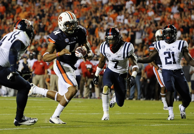 Oct 5, 2013; Auburn, AL, USA; Auburn Tigers quarterback Nick Marshall (14) runs the ball past Mississippi Rebels defense for a touchdown in the second quarter  at Jordan Hare Stadium. Mandatory Credit: Shanna Lockwood-USA TODAY Sports