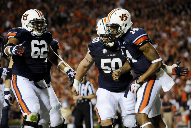 Oct 5, 2013; Auburn, AL, USA; Auburn Tigers quarterback Nick Marshall (14) celebrates his touchdown with offensive linesman Chad Slade (62) and Auburn Tigers defensive tackle Ben Bradley (50) during the second quarter against the Mississippi Rebels at Jordan Hare Stadium. Mandatory Credit: Shanna Lockwood-USA TODAY Sports