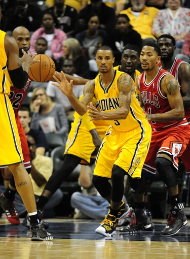 Oct 5, 2013; Indianapolis, IN, USA; Indiana Pacers point guard George Hill (3) passes the ball away while being defended by Chicago Bulls point guard Derrick Rose (1) at Bankers life Fieldhouse. Mandatory Credit: Marc Lebryk-USA TODAY Sports