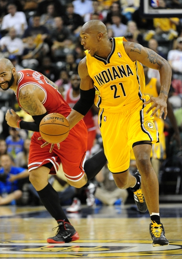 Oct 5, 2013; Indianapolis, IN, USA;  Indiana Pacers power forward David West (21) leads a break away from Chicago Bulls power forward Carlos Boozer (5) at Bankers life Fieldhouse. Final Score Pacers 76 and Bulls 82 Mandatory Credit: Marc Lebryk-USA TODAY Sports