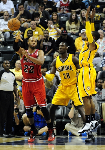 Oct 5, 2013; Indianapolis, IN, USA;  Chicago Bulls power forward Taj Gibson (22) passes around Indiana Pacers center Ian Mahinmi (28) and Indiana Pacers point guard George Hill (3) at Bankers Life Fieldhouse. Final Score Pacers 76 and Bulls 82. Mandatory Credit: Marc Lebryk-USA TODAY Sports