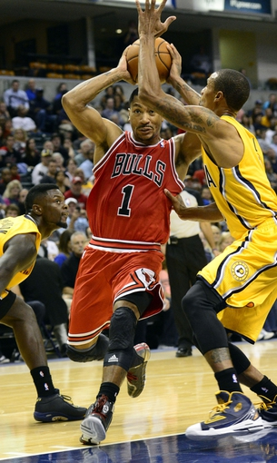 Oct 5, 2013; Indianapolis, IN, USA; Chicago Bulls point guard Derrick Rose (1) drives past Indiana Pacers point guard George Hill (3) at Bankers Life Fieldhouse. Bulls beat Pacers 82-76. Mandatory Credit: Marc Lebryk-USA TODAY Sports