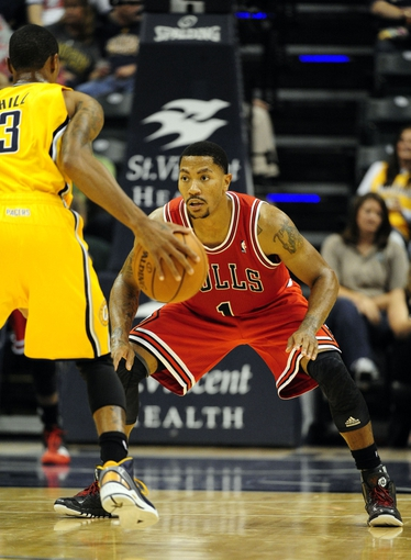 Oct 5, 2013; Indianapolis, IN, USA; Chicago Bulls point guard Derrick Rose (1) guards Indiana Pacers point guard George Hill (3) at Bankers Life Fieldhouse. Bulls beat Pacers 82-76. Mandatory Credit: Marc Lebryk-USA TODAY Sports