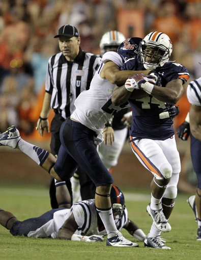Oct 5, 2013; Auburn, AL, USA; Auburn Tigers running back Cameron Artis-Payne (44) is tackled by Mississippi Rebels defensive back Cody Prewitt (25) during the second half at Jordan Hare Stadium.  The Tigers beat the Rebels 30-22. Mandatory Credit: John Reed-USA TODAY Sports