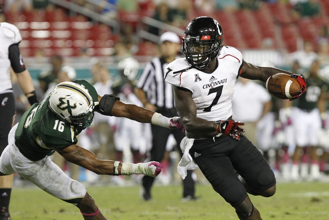 Oct 5, 2013; Tampa, FL, USA; Cincinnati Bearcats running back Tion Green (7) runs with the ball as South Florida Bulls linebacker Reshard Cliett (16) defends during the second half at Raymond James Stadium. South Florida Bulls defeated the Cincinnati Bearcats 26-20. Mandatory Credit: Kim Klement-USA TODAY Sports