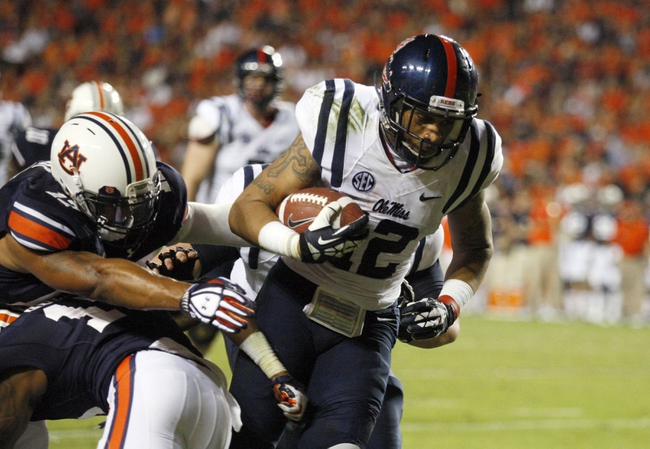 Oct 5, 2013; Auburn, AL, USA;  Mississippi Rebels receiver Donte Moncrief (12) gets past Auburn Tiger defenders and scores a touchdown during the fourth quarter at Jordan Hare Stadium.  The Tigers beat the Rebels 30-22. Mandatory Credit: John Reed-USA TODAY Sports