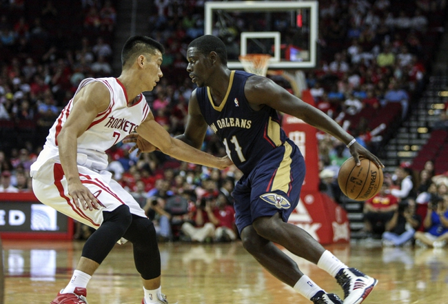 Oct 5, 2013; Houston, TX, USA; New Orleans Pelicans point guard Jrue Holiday (11) attempts to drive the ball past Houston Rockets point guard Jeremy Lin (7) during the second quarter at Toyota Center. Mandatory Credit: Troy Taormina-USA TODAY Sports