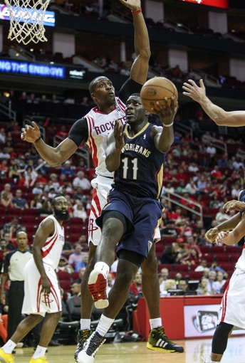 Oct 5, 2013; Houston, TX, USA; New Orleans Pelicans point guard Jrue Holiday (11) attempts to score during the second quarter as Houston Rockets center Dwight Howard (12) defends at Toyota Center. Mandatory Credit: Troy Taormina-USA TODAY Sports