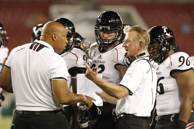 Oct 5, 2013; Tampa, FL, USA; Cincinnati Bearcats head coach Tommy Tuberville talks with associate head coach Robert Prunty and teammates against the South Florida Bulls  during the second half at Raymond James Stadium. South Florida Bulls defeated the Cincinnati Bearcats 26-20. Mandatory Credit: Kim Klement-USA TODAY Sports