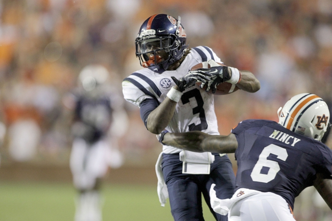 Oct 5, 2013; Auburn, AL, USA;  Mississippi Rebels running back Jeff Scott (3) gets past Auburn Tigers defensive back Jonathon Mincy (6) during the second half at Jordan Hare Stadium.  The Tigers beat the Rebels 30-22. Mandatory Credit: John Reed-USA TODAY Sports