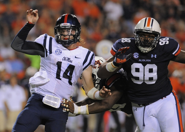 Oct 5, 2013; Auburn, AL, USA; Mississippi Rebels quarterback Bo Wallace (14) is tackled by Auburn Tigers defensive end Carl Lawson (55) and  defensive lineman Angelo Blackson (98) at Jordan Hare Stadium. The Tigers defeated the Rebels 33-20. Mandatory Credit: Shanna Lockwood-USA TODAY Sports