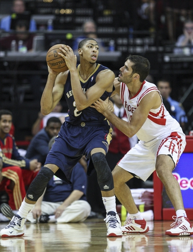 Oct 5, 2013; Houston, TX, USA; New Orleans Pelicans power forward Anthony Davis (23) controls the ball during the fourth quarter as Houston Rockets small forward Omri Casspi (18) defends at Toyota Center. The Pelicans defeated the Rockets 116-115. Mandatory Credit: Troy Taormina-USA TODAY Sports
