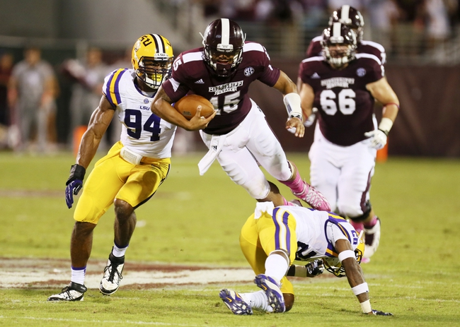 Oct 5, 2013; Starkville, MS, USA; Mississippi State Bulldogs quarterback Dak Prescott (15) gets hit down low by LSU Tigers cornerback Jalen Mills (28) during the game at Davis Wade Stadium.  LSU Tigers defeated the Mississippi State Bulldogs 59-26.  Mandatory Credit: Spruce Derden-USA TODAY Sports