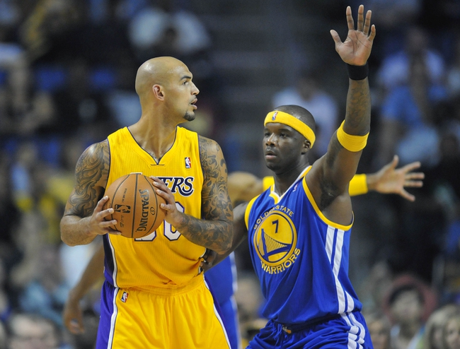 October 5, 2013; Ontario, CA, USA; Los Angeles Lakers center Robert Sacre (50) controls the ball against the defense of Golden State Warriors center Jermaine O'Neal (7) during the first half at Citizens Business Bank Arena. Mandatory Credit: Gary A. Vasquez-USA TODAY Sports