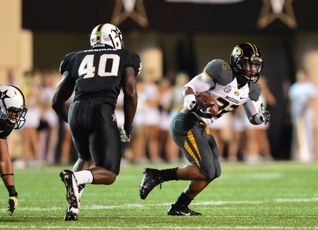 Oct 5, 2013; Nashville, TN, USA; Missouri Tigers running back Russell Hansbrough (32) runs with the ball against Vanderbilt Commodores linebacker Ja'karri Thomas (40) during the second half at Vanderbilt Stadium. The Tigers beat the Commodores 51-28. Mandatory Credit: Don McPeak-USA TODAY Sports