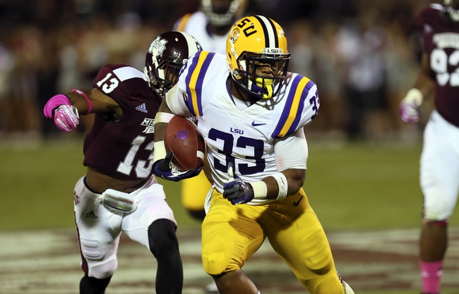 Oct 5, 2013; Starkville, MS, USA; LSU Tigers running back Jeremy Hill (33) advances the ball while followed by Mississippi State Bulldogs defensive back Cedric Jiles (13) at Davis Wade Stadium.  LSU Tigers defeated the Mississippi State Bulldogs 59-26.  Mandatory Credit: Spruce Derden-USA TODAY Sports