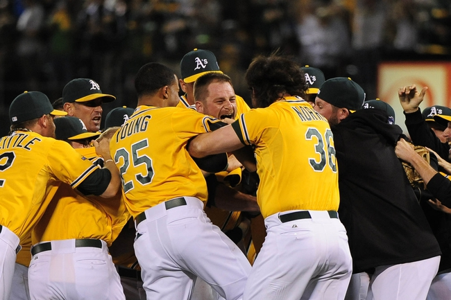 October 5, 2013; Oakland, CA, USA; Oakland Athletics catcher Stephen Vogt (21, center) is congratulated by his team after hitting the game-winning single to score left fielder Yoenis Cespedes (52, not pictured) after game two of the American League divisional series playoff baseball game against the Detroit Tigers at O.co Coliseum. The Athletics defeated the Tigers 1-0. Mandatory Credit: Kyle Terada-USA TODAY Sports