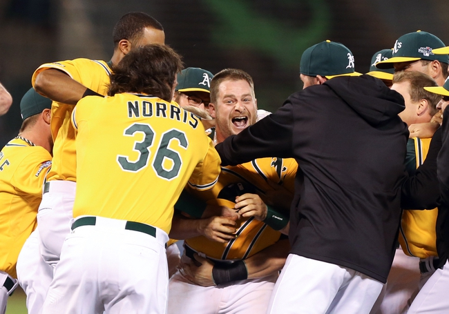 Oct 5, 2013; Oakland, CA, USA; Oakland Athletics catcher Stephen Vogt (21) is surrounded by teammates celebrating after hitting an RBI single for the walk off win against the Detroit Tigers in game two of the American League divisional series playoff baseball game at O.co Coliseum. The Oakland Athletics defeated the Detroit Tigers 1-0 with a walk off win. Mandatory Credit: Kelley L Cox-USA TODAY Sports