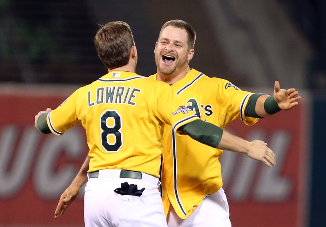 Oct 5, 2013; Oakland, CA, USA; Oakland Athletics catcher Stephen Vogt (21) celebrates with shortstop Jed Lowrie (8) after hitting an RBI single for the walk off win against the Detroit Tigers in game two of the American League divisional series playoff baseball game at O.co Coliseum. The Oakland Athletics defeated the Detroit Tigers 1-0 with a walk off win. Mandatory Credit: Kelley L Cox-USA TODAY Sports