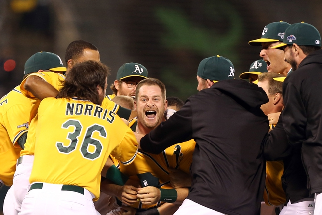 Oct 5, 2013; Oakland, CA, USA; Oakland Athletics catcher Stephen Vogt (21) celebrates with teammates after hitting an RBI single for the walk off win against the Detroit Tigers in game two of the American League divisional series playoff baseball game at O.co Coliseum. The Oakland Athletics defeated the Detroit Tigers 1-0 with a walk off win. Mandatory Credit: Kelley L Cox-USA TODAY Sports