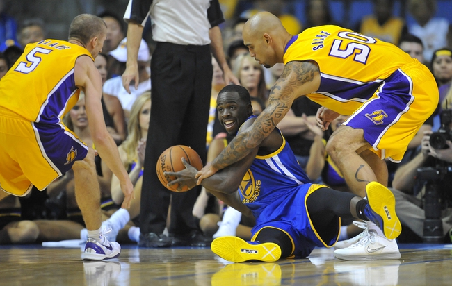 October 5, 2013; Ontario, CA, USA; Golden State Warriors forward Draymond Green (23) is defended by Los Angeles Lakers center Robert Sacre (50) and point guard Steve Blake (5) during the second half at Citizens Business Bank Arena. Mandatory Credit: Gary A. Vasquez-USA TODAY Sports