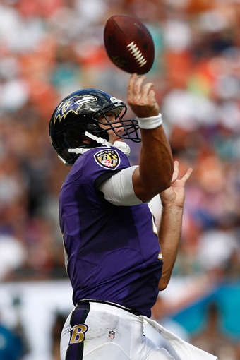 Oct 6, 2013; Miami Gardens, FL, USA; Baltimore Ravens quarterback Joe Flacco (5) throws an interception in the second half against the Miami Dolphins at Sun Life Stadium. Mandatory Credit: Robert Mayer-USA TODAY Sports