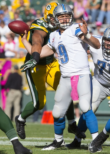 Oct 6, 2013; Green Bay, WI, USA; Green Bay Packers linebacker Nick Perry (53) knocks the football away from Detroit Lions quarterback Matthew Stafford (9) during the fourth quarter at Lambeau Field. The Packers won 22-9. Mandatory Credit: Jeff Hanisch-USA TODAY Sports