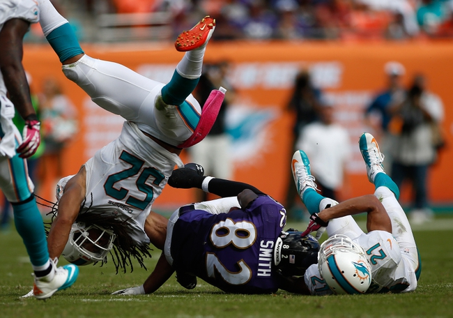 Oct 6, 2013; Miami Gardens, FL, USA; Baltimore Ravens wide receiver Torrey Smith (82) is tackled by Miami Dolphins cornerback Brent Grimes (21) and outside linebacker Philip Wheeler (52) in the second half at Sun Life Stadium. Mandatory Credit: Robert Mayer-USA TODAY Sports