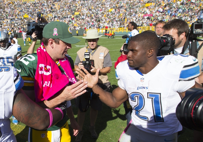 Oct 6, 2013; Green Bay, WI, USA; Green Bay Packers quarterback Aaron Rodgers (12) talks with Detroit Lions running back Reggie Bush (21) following the game at Lambeau Field. The Packers won 22-9. Mandatory Credit: Jeff Hanisch-USA TODAY Sports